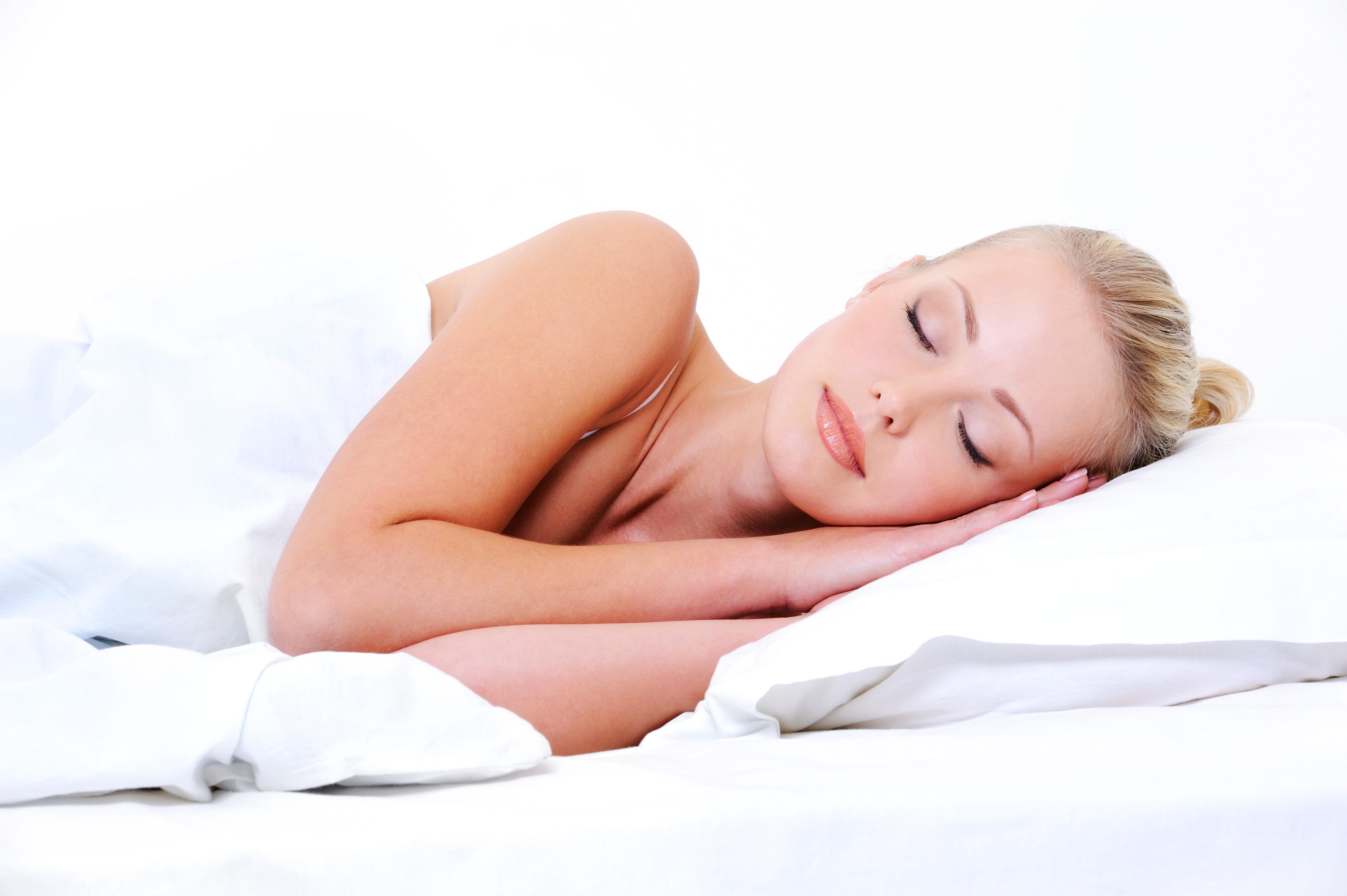 Beautiful young sleeping woman seeing sweet dreams